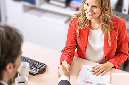 versicherungscheck24.de – Hausratversicherung wechseln – Beraterin schüttelt Hand von Mandanten
