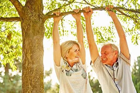 versicherungscheck24.de – Pflegeversicherung – Beiträge – Seniorenpaar macht Spaß im Park