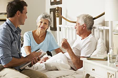 versicherungscheck24.de – Pflegeversicherung – Beitragsbemessungsgrenze – Senior wird am Krankenbett freundlich beraten