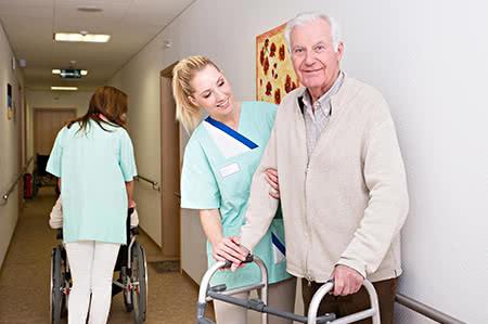 versicherungscheck24.de – Pflegeversicherung – Pflegestufen – Rentner im Seniorenheim mit freundlicher Pflegerin