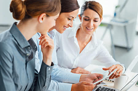 versicherungscheck24.de – Freiwillige Pflegeversicherung – Drei Frauen sitzen an Schreibtisch und schauen sich Dokumente an