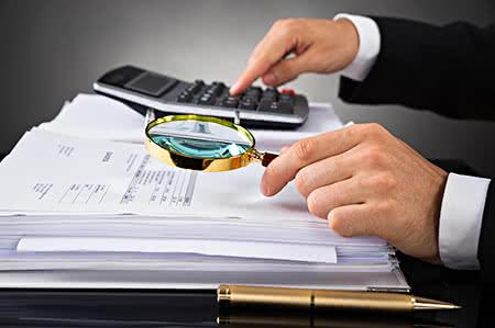 versicherungscheck24.de – Pflegeversicherung günstig abschließen – Mann am Schreibtisch nimmt Dokumente unter die Lupe