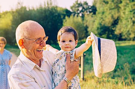 versicherungscheck24.de – Private Pflegeversicherung – Senior hält seine kleine Enkelin auf dem Arm