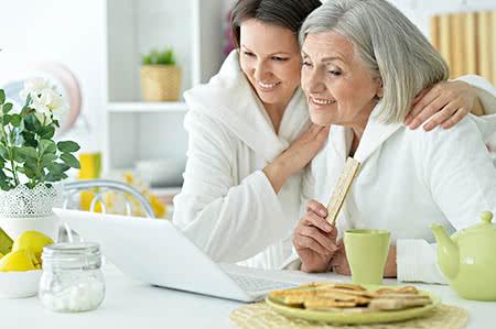 versicherungscheck24.de – Private Pflegeversicherung – Seniorin mit Tochter vor dem Laptop